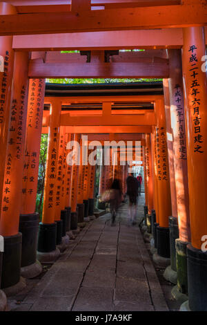 Two people walk down the vibrant torii path while another one walks up. Hits of lush vegetation can be seen in between the torii gaps.