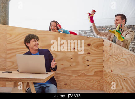 Young businessman working on laptop with colleagues playing hand puppets behind wooden wall - Stock Photo