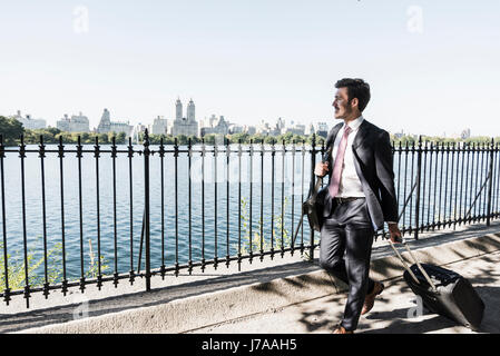 USA, New York City, businessman walking at the waterfront - Stock Photo