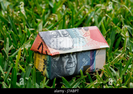 Origami house made with Australian Notes sitting on grass - Stock Photo