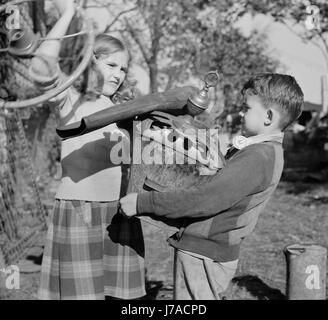 Young children collecting scrap for donation to their war industries, 1942. - Stock Photo