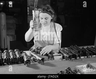 Woman worker using an electric screwdriver to assemble toy trains, 1942. - Stock Photo