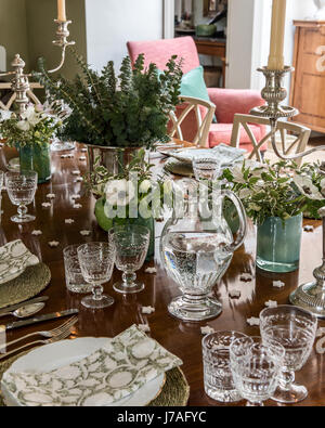 Detail of block-printed napkins, heirloom china, silver and Stuart crystal adorn a festively laid table - Stock Photo