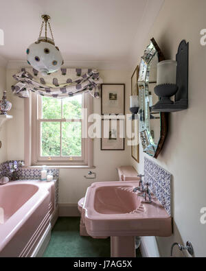 Pink enamelled cast iron bath and basin in bathroom with Fired Earth tiles and ornate gilt mirror - Stock Photo