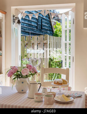 Sponge cake, enamel teapot and pink peonies on striped table cloth from Susie Watson Designs