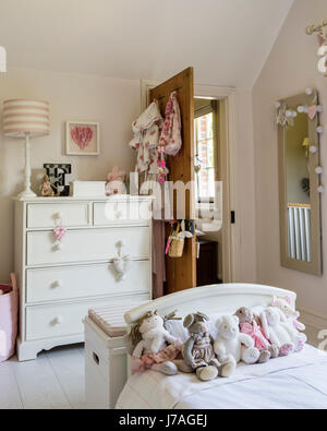 Assorted teddy bears on bed in childs bedroom, the chest of drawers is painted in Farrow & Ball's Pointing by Fairlily - Stock Photo