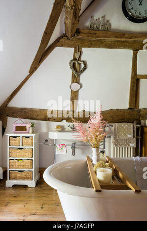 Vaulted bathroom with ancient beams, exposed brick wall and roll-top French bath. - Stock Photo
