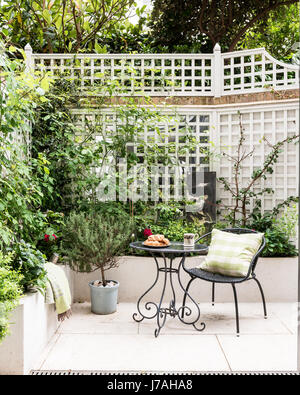 Chair and table in courtyard garden of Victorian terrace, London - Stock Photo