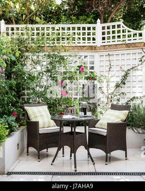 Wicker furniture in courtyard garden of Victorian terrace, London - Stock Photo