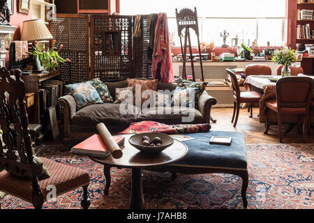 Drawing room with a Victorian bergere sofa and a Charles II style chair. Beyond the ornate screen are paint materials - Stock Photo