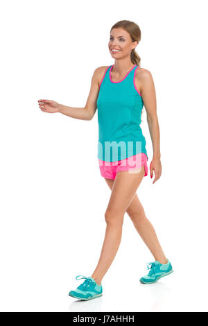 Smiling beautiful young woman in pink shorts turquoise tank top and sneakers walking and looking away, Front side - Stock Photo