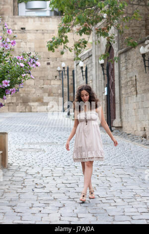 Full length portrait of curlie young girl wearing biege romantic dress strolling through old streets of Inner City - Stock Photo