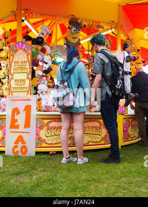 A young couple hold hands beside a fairground stall - Stock Photo