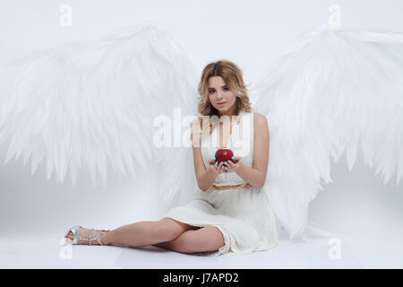 beautiful young model with big angel wings sitting in the studio - Stock Photo