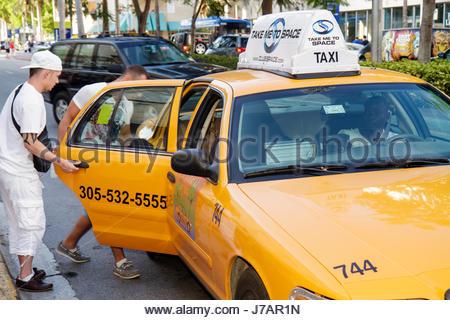 Miami Beach Florida Washington Avenue taxi cab transportation man men enter ride vehicle yellow - Stock Photo