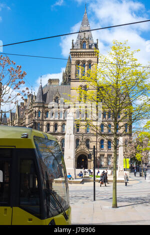War memorial outside the rear entrance of Town Hall with passing tram on St Peter's Square in Manchester UK - Stock Photo