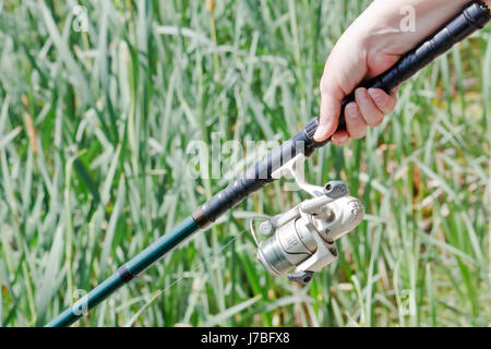 hand fishing rod possession holding woman bread hand hands finger spare time - Stock Photo
