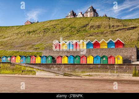 Rows of colorful beach huts on the promenade at Whitby Sands, Whitby, North Yorkshire, England, UK, on a beautiful - Stock Photo