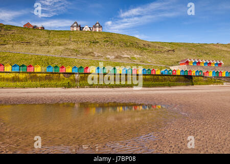 Beach huts lining the promenade and reflecting in a pool at North Beach, Whitby, North Yorkshire, England, UK, on - Stock Photo