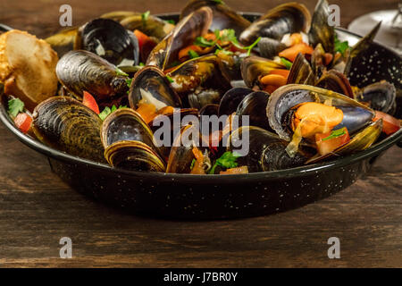 Skillet of marinara mussels on rustic background - Stock Photo