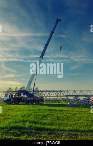 Car crane with risen telescopic boom outdoors on the construction site. - Stock Photo