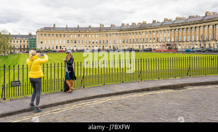 Tourists taking pictures in front of the Royal Crescent in Bath, UK - Stock Photo