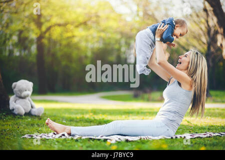 Delighted mother with her one year old son outdoors in a park - Stock Photo