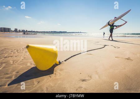 Yellow conical buoy on the beach of Les Sables d'Olonne at low tide - Stock Photo