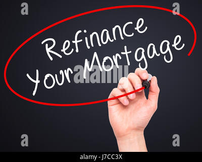Man Hand writing Refinance Your Mortgage with black marker on visual screen. Isolated on black. Business, technology, - Stock Photo