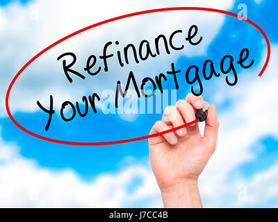 Man Hand writing Refinance Your Mortgage with black marker on visual screen. Isolated on sky. Business, technology, - Stock Photo