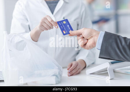 Man at the pharmacy making purchases with a credit card, he is giving the card to the female pharmacist, hands close - Stock Photo