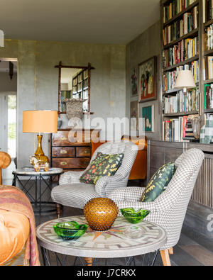 Pair of upholstered chairs with bookcase and glass ornaments - Stock Photo