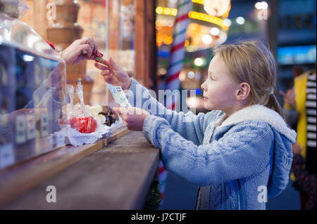 Girl buying sweets, Christmas Market, Leicester Square, London - Stock Photo