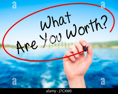 Man Hand writing What Are You Worth? with black marker on visual screen. Isolated on nature. Business, technology, - Stock Photo