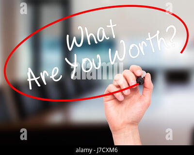 Man Hand writing What Are You Worth? with black marker on visual screen. Isolated on office. Business, technology, - Stock Photo