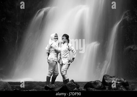 Girls posing at surreal waterfall for black and white portrait photo with ethereal silky smooth waterfall in the - Stock Photo