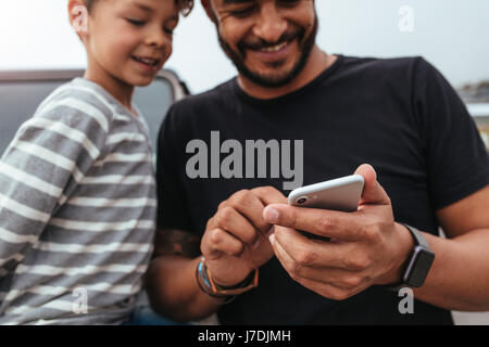 Close up of happy father and son in front of the car looking at the mobile phone. Young man and little boy using - Stock Photo