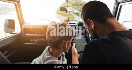 Close up rear view of father and son looking at map on digital tablet while travel by car. Family looking for road - Stock Photo