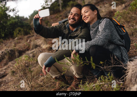 Couple in love sitting on mountain trail and taking selfie. Young man and woman hiking in countryside and talking self portrait with mobile phone.