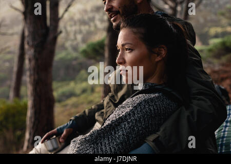 Young asian woman sitting outdoors with her boyfriend. Young couple resting after hike. - Stock Photo