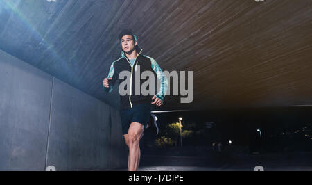 Young man jogging at night in city. Fit male athlete running under a bridge. - Stock Photo