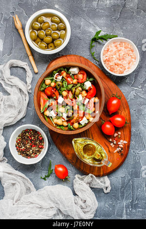 Spring vegetable salad with arugula, cherry tomatoes, chickpeas, olives and feta cheese. Healthy, vegan, detox food. - Stock Photo