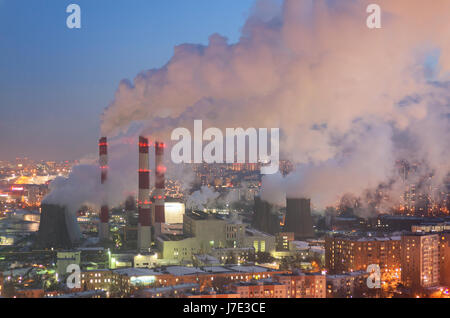 Steam and smoke from the chimneys and cooling towers city Central Heating and Power Plant. The view from the heights in the twilight, winter