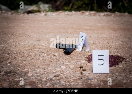 The crime scene, murder, investigation, gun and shell finds the police, puts tags rip shells and guns, traces of - Stock Photo