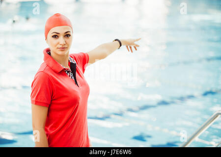 Portrait of female coach with a stop watch and clipboard by pool at leisure center - Stock Photo