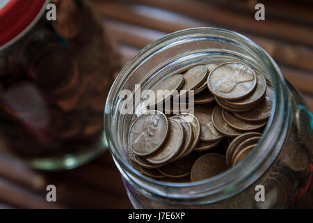 Jar filled with Pennies us currency one cent piece - Stock Photo
