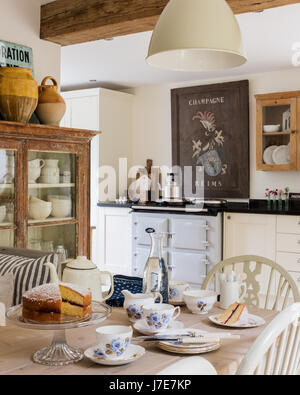 Vintage French wooden champagne sign above Aga in rustic kitchen with French feel. The table is laid for tea with - Stock Photo