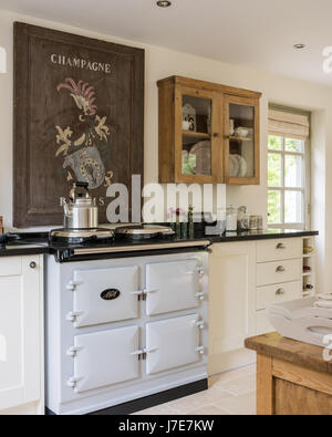 Vintage French wooden champagne sign above Aga in rustic kitchen with French feel. The display cupboard is from - Stock Photo