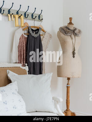 Elegant mannequin in bedroom with rustic coat hooks and cushions from Cabbages & Roses - Stock Photo