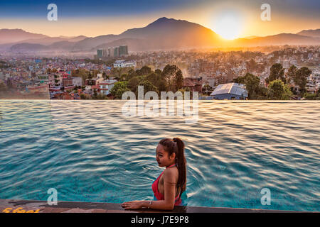 Girl is posing at pool on  the 8th floor pool deck at the Shambala Hotel in Kathmandu,Nepal at sunset with pool - Stock Photo